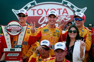 Joey Logano celebrates winning the Toyota Owners 400 with his team and wife Brittany