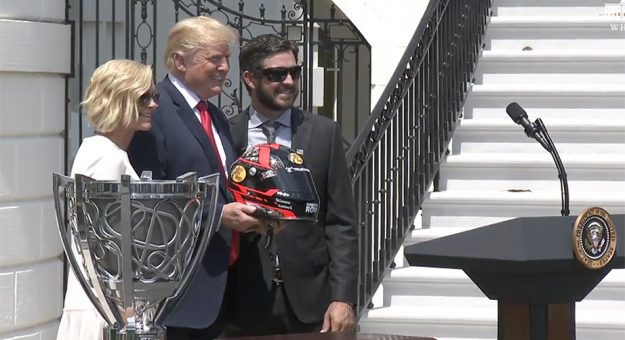 Martin Truex Jr. and girlfriend Sherry Pollex offer a gift of a replica helmet to President Trump.