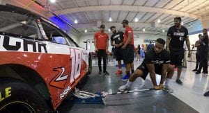 A member of the Pit Crew Combine lifts a car up with the jack during a mock pit stop.