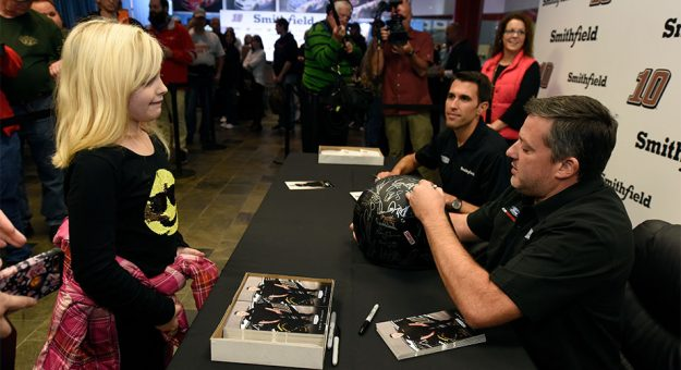 Tony Stewart signs an autograph for a young fan