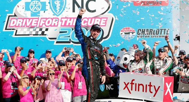 Chase Briscoe stands on his car and pumps his fist amid confetti in victory lane, surrounded by breast cancer survivors in pink shirts