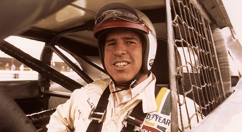David Pearson smiles from inside the race car during the 1970s with his helmet on and bubble eye shields on top of his helmet.