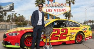 LAS VEGAS, NV - NOVEMBER 28:  Monster Energy NASCAR Cup Series Champion Joey Logano poses with the Monster Energy NASCAR Cup Series championship trophy in front of the Welcome to Fabulous Las Vegas sign during NASCAR Champion's Week on November 28, 2018 in Las Vegas, Nevada.  (Photo by Brian Lawdermilk/Getty Images) | Getty Images