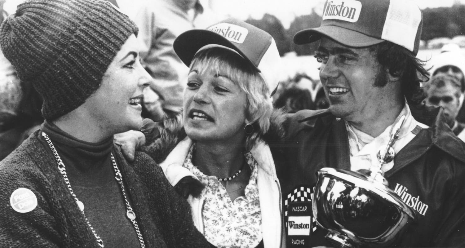 MARTINSVILLE, VA - 1976: Actress Elizabeth Taylor joins Geoff Bodine in victory lane after Bodine won the NASCAR Modified portion of the Cardinal 500 at Martinsville Speedway. (Photo by ISC Images & Archives via Getty Images)
