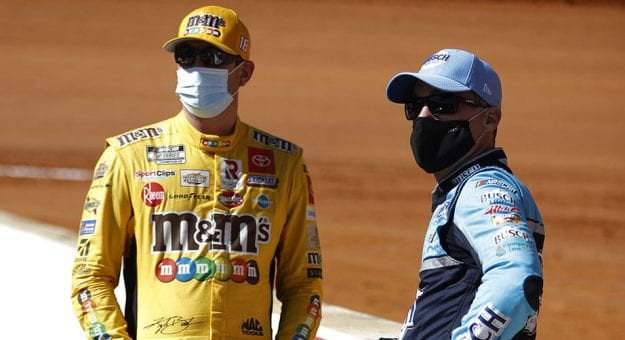 BRISTOL, TENNESSEE - MARCH 29: Kyle Busch, driver of the #18 M&M's Messages Toyota, and Kevin Harvick, driver of the #4 Busch Light Ford, talk on the grid prior to the NASCAR Cup Series Food City Dirt Race at Bristol Motor Speedway on March 29, 2021 in Bristol, Tennessee. (Photo by Chris Graythen/Getty Images) | Getty Images