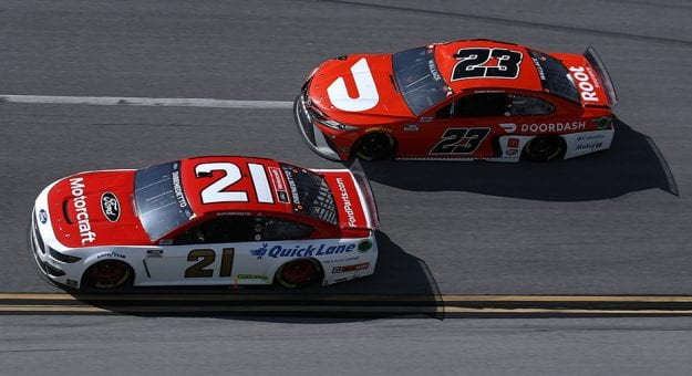 TALLADEGA, ALABAMA - APRIL 25: Bubba Wallace, driver of the #23 DoorDash Toyota, and Matt DiBenedetto, driver of the #21 Motorcraft Quick Lane Ford, race during the NASCAR Cup Series  GEICO 500 at Talladega Superspeedway on April 25, 2021 in Talladega, Alabama. (Photo by Sean Gardner/Getty Images) | Getty Images